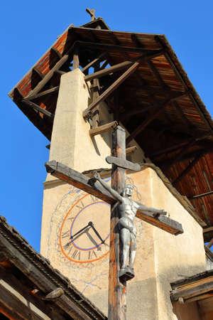 Close-up on the bell tower of Saint Sebastien Church with the Cross of Jesus Christ, Ceillac, Queyras Regional Natural Park, Southern Alps, France Stock fotó