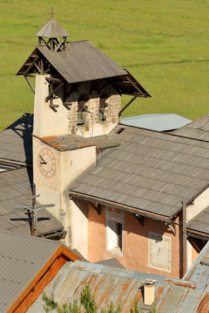 Aerial view of the bell tower of Saint Sebastien Church, with a Cross of Jesus Christ and a sundial, Ceillac, Queyras Regional Natural Park, Southern Alps, France Stock fotó