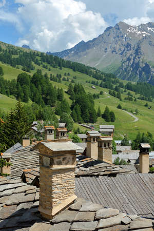 Traditional roofs and chimneys in Saint Veran village, with mountain range covered with snow and pine tree forests in the background, Queyras Regional Natural Park, Southern Alps, France Stock fotó