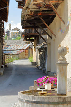 A traditional wooden fountain with traditional wooden balconies and the church in the background in Saint Veran village, Queyras Regional Natural Park, Southern Alps, France