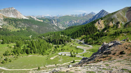 Panoramic view towards the Northern side of Izoard Pass, with a winding road, pine tree forests and mountain range covered with snow in the background, Queyras Regional Natural Park, Southern Alps, France
