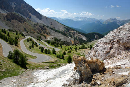 The Southern side of Izoard pass with the winding road and the dramatic landscape called Casse deserte (a lunar and rocky circus), Queyras Regional Natural Park, Southern Alps, France, Europe, hautes alpes