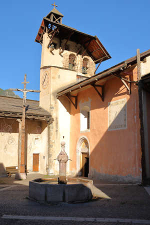 The main Square of Ceillac village with a traditional fountain, Saint Sebastien Church and the Cross of Jesus Christ, Ceillac, Queyras Regional Natural Park, Southern Alps, France Stock fotó