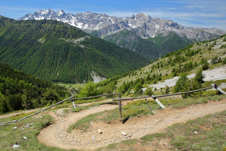 Hiking path  leading to Fromage pass above Ceillac village, Queyras Regional Natural Park, Southern Alps, France, with mountain range covered with snow and pine tree forests in the background Stock fotó