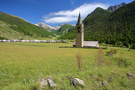 Sainte Cecile Church with Ceillac village, pine tree forests and mountain range covered with snow in the background, Ceillac, Queyras Regional Natural Park, Southern Alps, France