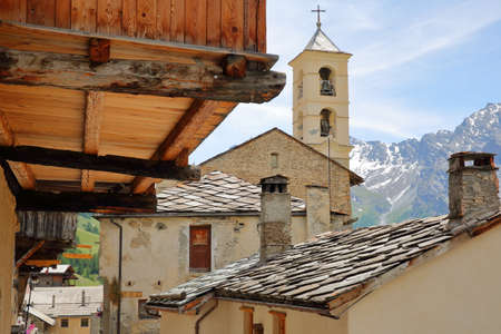 Traditional wooden houses and the church in Saint Veran village, with mountain range covered with snow in the background, Queyras Regional Natural Park, Southern Alps, France