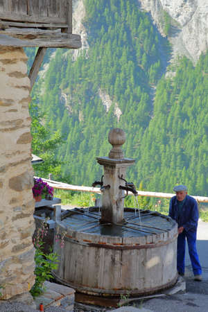 SAINT VERAN, QUEYRAS, FRANCE - JUNE 30, 2019: A traditional wooden fountain and an old local man, Saint Veran, Queyras Regional Natural Park, Southern Alps Sajtókép