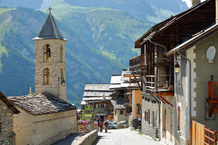 SAINT VERAN, QUEYRAS, FRANCE - JULY 1, 2019: Traditional houses with wooden balconies, with the Reformee church on the left, Saint Veran, Queyras Regional Natural Park, Southern Alps, France Sajtókép