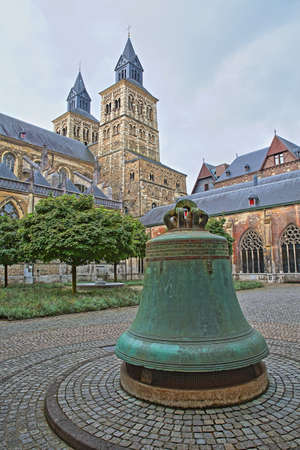 MAASTRICHT, NETHERLANDS - AUGUST 03, 2019: The inner courtyard of  the basilica of Saint Servatius, 11th century Cathedral, Vrijthof Square, with a large bell and the clock towers in the background
