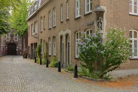 MAASTRICHT, NETHERLANDS - AUGUST 03, 2019: De Bosquetplein, a cobbled street leading to the entrance of Natural History Museum, with typical 17th century houses