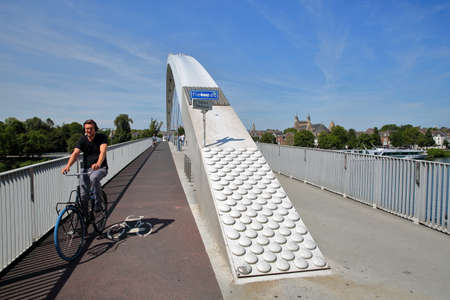 MAASTRICHT, NETHERLANDS - AUGUST 04, 2019: A cyclist on the Hoge Brug, a pedestrian and bicycle suspension bridge over the Meuse river, with the basilica of our Lady in the background Redakční
