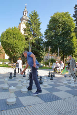 SARAJEVO, BOSNIA AND HERZEGOVINA - SEPTEMBER 15, 2019: Local chess players gathering in Trg Oslobodenja (Liberation Square) and playing with a large scale Chess Board, with the Orthodox Cathedral of the Nativity of the Theotokos in the background