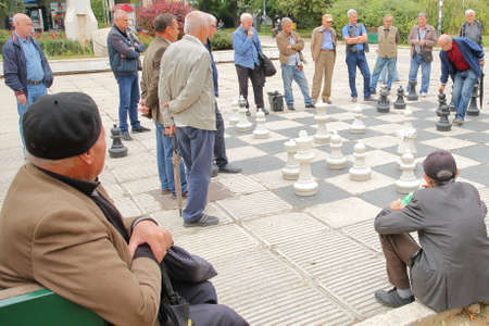 SARAJEVO, BOSNIA AND HERZEGOVINA - SEPTEMBER 23, 2019: Local chess players gathering in Trg Oslobodenja (Liberation Square) and playing with a large scale Chess Board