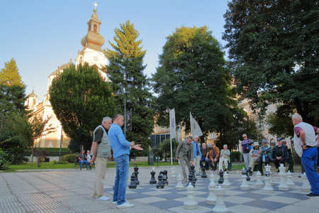 SARAJEVO, BOSNIA AND HERZEGOVINA - SEPTEMBER 13, 2019: Local chess players gathering in Trg Oslobodenja (Liberation Square) and playing with a large scale Chess Board, with the Orthodox Cathedral of the Nativity of the Theotokos in the background