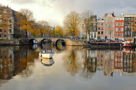 AMSTERDAM, NETHERLANDS - NOVEMBER 19, 2019: Reflections of colorful heritage buildings and houseboats, at the junction between Amstel river and Prinsengracht Canal Standard-Bild - 139139345