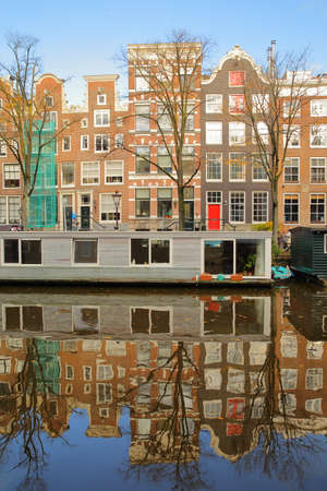 AMSTERDAM, NETHERLANDS - NOVEMBER 19, 2019: Reflections of colorful heritage buildings and houseboats, overlooking Prinsengracht Canal Standard-Bild - 139139346