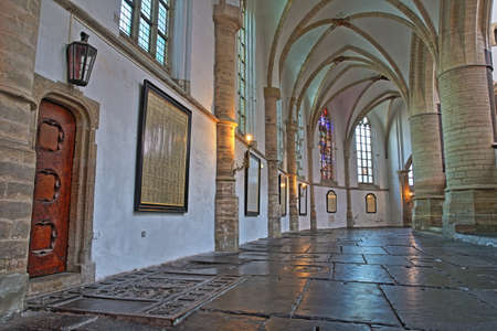 HAARLEM, NETHERLANDS - NOVEMBER 29, 2019: The interior of St Bavokerk Church, with  an alignement of columns and arches and gravestones in the foreground Editorial