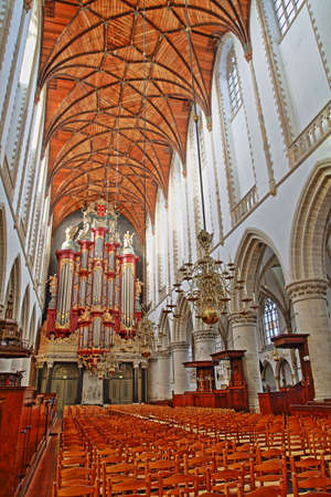 HAARLEM, NETHERLANDS - NOVEMBER 29, 2019: The interior of St Bavokerk Church, with a wooden vaulted ceiling and the organ (built by Christian Muller in 1738)