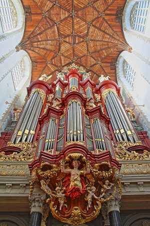 HAARLEM, NETHERLANDS - NOVEMBER 29, 2019: The interior of St Bavokerk Church, with a wooden vaulted ceiling  and the organ (built by Christian Muller in 1738) with details of sculptures Editorial