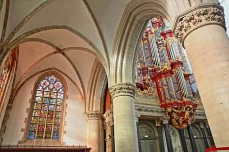 HAARLEM, NETHERLANDS - NOVEMBER 29, 2019: The interior of St Bavokerk Church, with columns, stained glasses and the organ (built by Christian Muller in 1738)