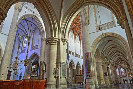 HAARLEM, NETHERLANDS - NOVEMBER 29, 2019: The interior of St Bavokerk Church, with the nave and the transept viewed through arches and columns