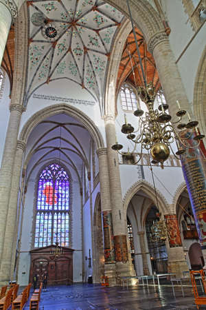 HAARLEM, NETHERLANDS - NOVEMBER 29, 2019: The interior of St Bavokerk Church, with the transept, stained glasses and the decorated vaulted  ceiling