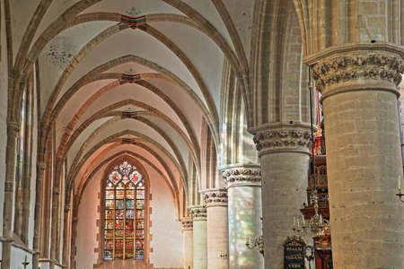 HAARLEM, NETHERLANDS - NOVEMBER 29, 2019: The interior of St Bavokerk Church, with stained glasses and alignement of columns and arches