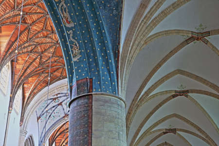 HAARLEM, NETHERLANDS - NOVEMBER 29, 2019: The interior of St Bavokerk Church, with close-up on the vaulted ceiling and a decorated column in the foreground Editorial