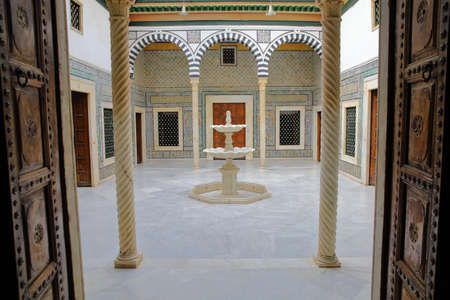 TUNIS, TUNISIA - DECEMBER 08, 2019: Small patio with a marble fountain inside the Bardo Museum, with ceramics, columns and arcades Standard-Bild - 141072870