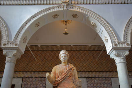 TUNIS, TUNISIA - DECEMBER 08, 2019: The Carthage room inside the Bardo Museum with close-up on a roman sculpture  with arcades and columns Editorial