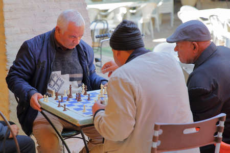 TOZEUR, TUNISIA - DECEMBER 19, 2019: Locals playing chess inside a cafe in Tozeur