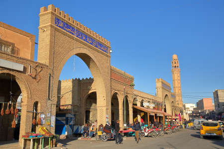 TOZEUR, TUNISIA - DECEMBER 20, 2019: The lively main street of Tozeur (Habib Bourguiba Avenue), with cafes, a minaret and arcades decorated with patterns of bricks Standard-Bild - 141072876