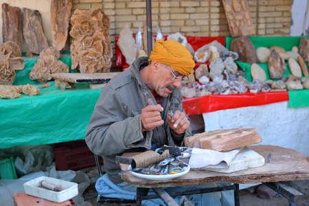 TOZEUR, TUNISIA - DECEMBER 20, 2019: A local craftsman at work (Habib Bourguiba avenue)