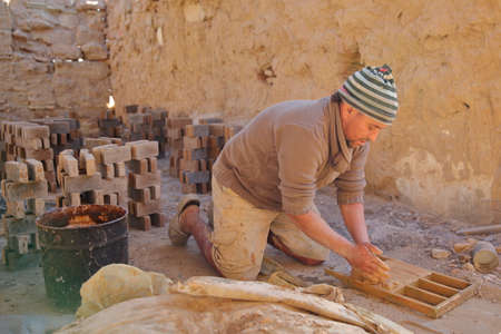 TOZEUR, TUNISIA - DECEMBER 20, 2019: A local worker making bricks in a traditional way in a brick factory. A wooden frame is used to mold the bricks.