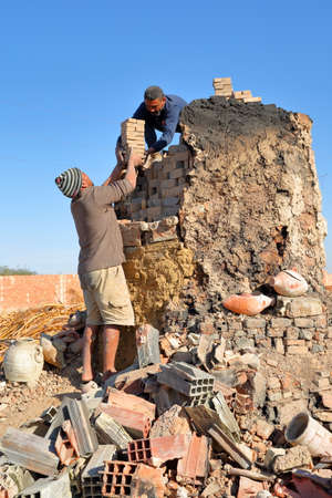 TOZEUR, TUNISIA - DECEMBER 20, 2019: Two local workers making bricks in a traditional way in a brick factory. They put the dried bricks inside an oven
