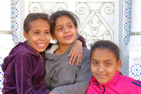 TOZEUR, TUNISIA - DECEMBER 20, 2019: portrait of three smiling little girls in Tozeur, with a traditional door in the background