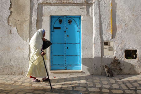 TUNIS, TUNISIA - DECEMBER 09, 2019: Typical cobbled and narrow street (Pacha street) inside the historical medina of Tunis, with a colorful door and a woman traditionaly dressed in white Standard-Bild - 141072886