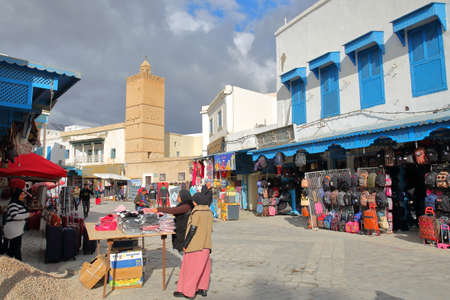 KAIROUAN, TUNISIA - DECEMBER 09, 2019: The lively main street inside the medina of Kairouan, with shops and market stalls Standard-Bild - 141072887