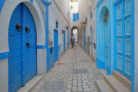 KAIROUAN, TUNISIA - DECEMBER 09, 2019: Typical cobbled and narrow street  inside the historical medina of Kairouan, with blue and white colors and a local man cycling