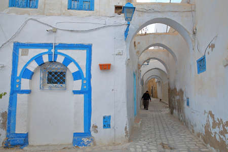 KAIROUAN, TUNISIA - DECEMBER 09, 2019: Typical cobbled and narrow street  inside the historical medina of Kairouan, with blue and white colors and arcades Editorial