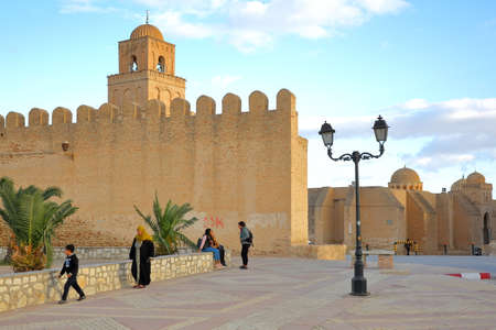 KAIROUAN, TUNISIA - DECEMBER 09, 2019: The Great Mosque of Kairouan viewed from outside the ramparts and with local people in the foreground Editorial