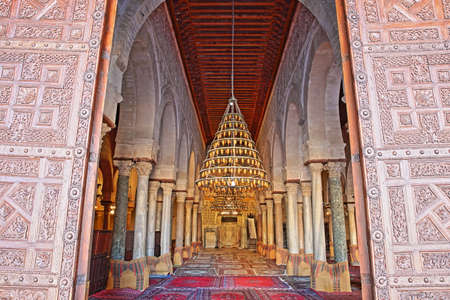 KAIROUAN, TUNISIA - DECEMBER 10, 2019: The entrance to the prayer room of the Great Mosque of Kairouan, with the carved wooden door in the foreground Editorial