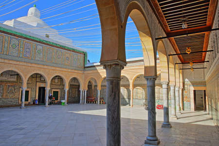 KAIROUAN, TUNISIA - DECEMBER 10, 2019: The inner courtyard of the Abou Zamaa Zaouia (Barber's mosque or Sidi Sahbi mosque), with colorful tiles, columns and arcades