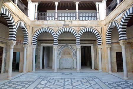 KAIROUAN, TUNISIA - DECEMBER 10, 2019: The inner courtyard of the Sidi Abid El Ghariani Zaouia, with columns and arcades