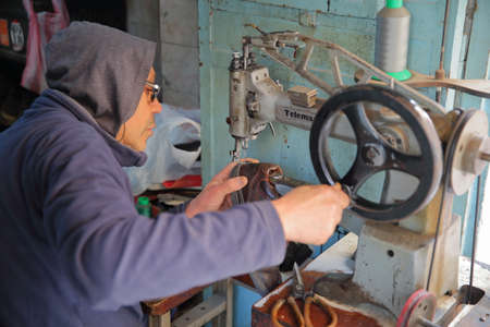 KAIROUAN, TUNISIA - DECEMBER 10, 2019: A cobbler at work inside the medina Editorial