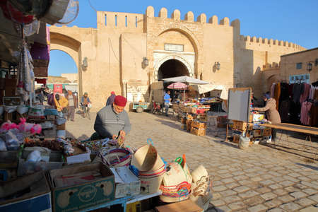 KAIROUAN, TUNISIA - DECEMBER 11, 2019: The lively main street inside the medina of Kairouan, with shops, market stalls and the ramparts