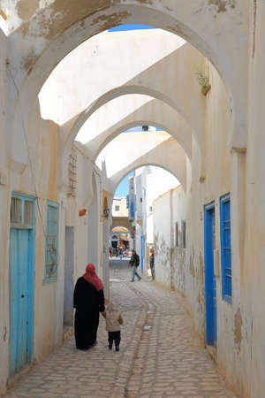 KAIROUAN, TUNISIA - DECEMBER 11, 2019: Typical cobbled and narrow street  inside the historical medina of Kairouan, with blue and white colors and arcades Editorial