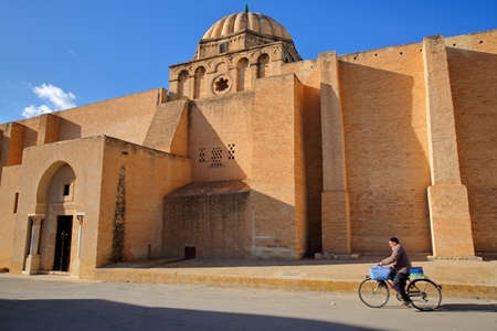 KAIROUAN, TUNISIA - DECEMBER 11, 2019: The rear entrance to the prayer room of the Great Mosque with a local man cycling