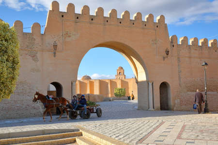 KAIROUAN, TUNISIA - DECEMBER 11, 2019: Entrance gate to Kairouan (eastern side of the city), with the dome and the minaret of the Great Mosque in the background and a traditional carriage with a horse in the foreground