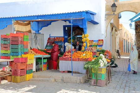 KAIROUAN, TUNISIA - DECEMBER 12, 2019: A traditional fruit and vegetable little shop, located inside the medina, with a woman traditionally dressed in white Standard-Bild - 141072911
